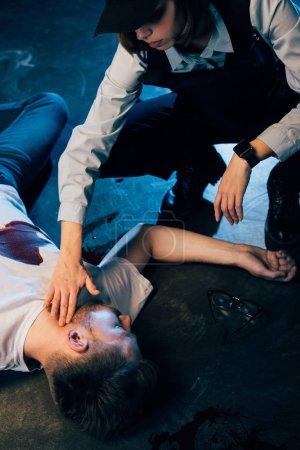 Photo pour Vue recadrée de l'enquêteur vérifiant le pouls d'un homme mort sur les lieux du crime - image libre de droit