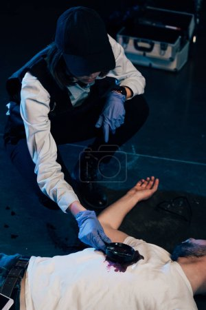 Photo for Investigator looking at wound on corpse with magnifying glass at crime scene - Royalty Free Image