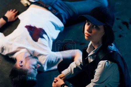 Foto de Overhead view of investigator sitting near cadaver at crime scene - Imagen libre de derechos
