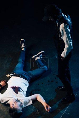 Photo pour Vue aérienne de l'enquêteur en uniforme debout près du cadavre sur les lieux du crime - image libre de droit