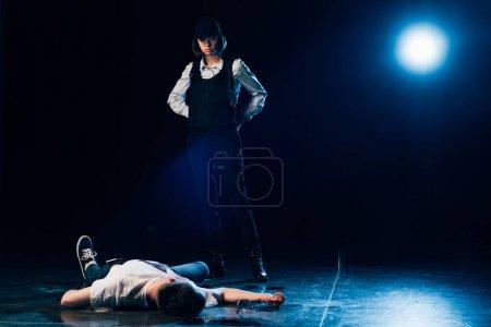 Photo pour Vue complète de l'enquêteur en uniforme debout près du cadavre sur les lieux du crime - image libre de droit