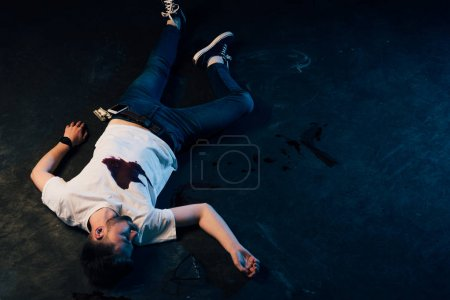 Overhead view of dead man with blood on t-shirt ly...