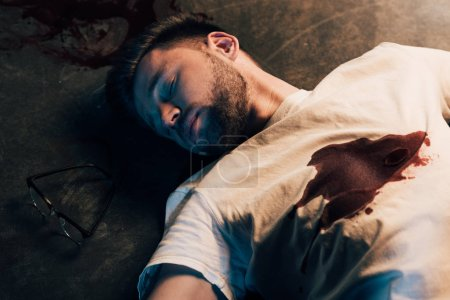 Photo pour Homme mort avec du sang sur le t-shirt sur l'étage à la scène de crime - image libre de droit