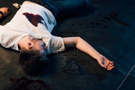 Foto de Dead man with blood on t-shirt on floor at crime scene - Imagen libre de derechos