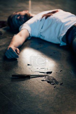 Foto de Selective focus of dead man with blood on t-shirt on floor at crime scene - Imagen libre de derechos