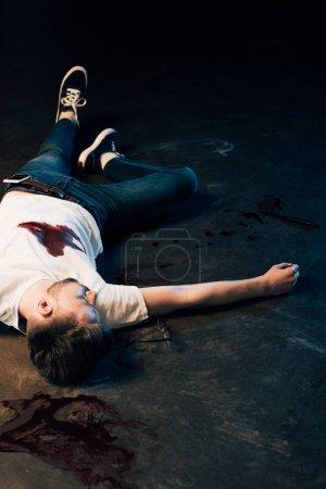 Foto de Dead man with smartphone in pocket on floor at crime scene - Imagen libre de derechos