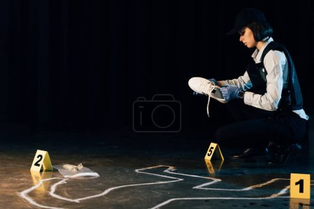 Photo pour Investigator in uniform holding shoe at crime scene - image libre de droit