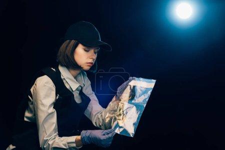 Photo pour Enquêteur dans des gants en caoutchouc tenant un sac ziploc avec billet en dollar sur les lieux du crime - image libre de droit