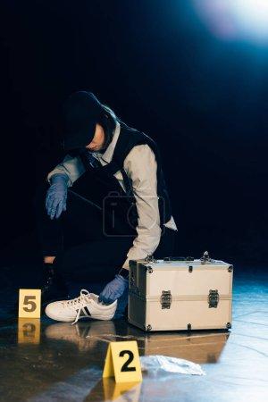 Photo pour Investigator in uniform holding shoe at crime scene - image libre de droit