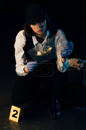 Photo for Investigator in rubber gloves holding ziploc bag with dollar banknote at crime scene - Royalty Free Image