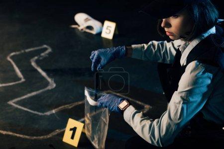 Photo pour Enquêteur en uniforme recueillant des preuves sur les lieux du crime - image libre de droit