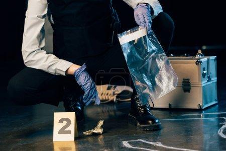 Photo pour Vue partielle de l'enquêteur en uniforme recueillant des preuves sur les lieux du crime - image libre de droit