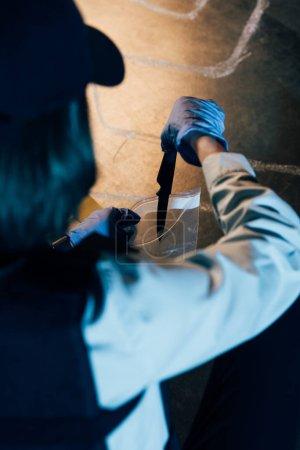 Photo pour Foyer sélectif de l'enquêteur mettre un couteau dans un sac ziploc sur les lieux du crime - image libre de droit