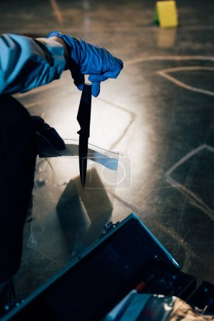 Photo for Partial view of investigator putting evidence in ziploc bag at crime scene - Royalty Free Image