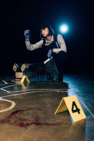 Photo pour Enquêteur tenant un couteau et un sac ziploc sur les lieux du crime - image libre de droit