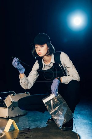 Photo for Investigator holding knife and ziploc bag at crime scene - Royalty Free Image