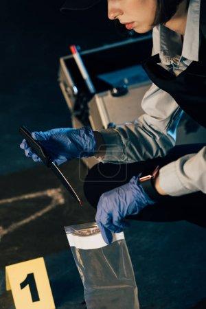 Photo pour Vue recadrée de l'enquêteur tenant un couteau et un sac ziploc sur les lieux du crime - image libre de droit