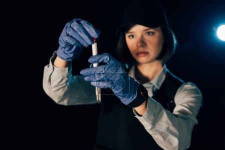Photo pour Foyer sélectif de l'enquêteur dans des gants de caoutchouc tenant écouvillonnage et éprouvette sur les lieux du crime - image libre de droit