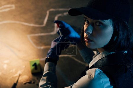 investigator in rubber gloves looking at camera at crime scene