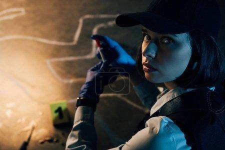 Photo pour Enquêteur en gants de caoutchouc regardant la caméra sur la scène de crime - image libre de droit