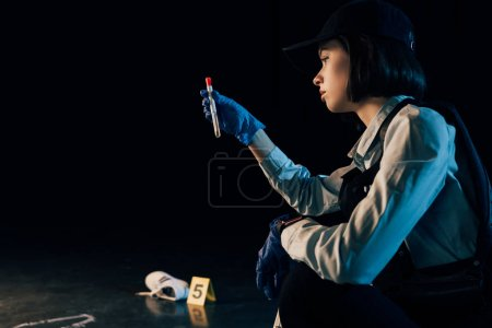 Photo for Pensive investigator in rubber gloves holding test tube at crime scene - Royalty Free Image