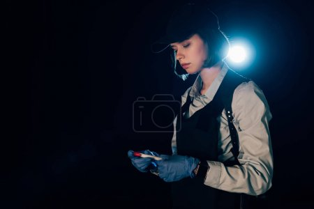 Photo for Investigator in rubber gloves holding test tube at crime scene - Royalty Free Image