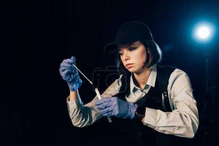 Photo pour Enquêteur dans des gants en caoutchouc tenant l'écouvillon et le tube d'essai à la scène de crime - image libre de droit