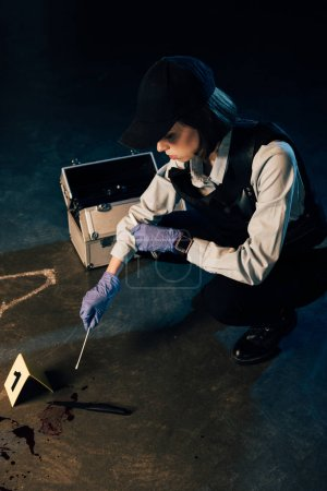 Photo for Investigaror in gloves holding test tube and swab at crime scene - Royalty Free Image
