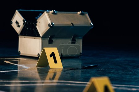 Photo for Selective focus of knife, investigation kit, chalk outline and evidence markers at crime scene - Royalty Free Image