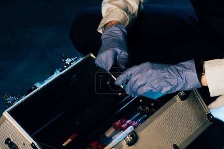 Photo for Cropped view of investigator in rubber gloves with investigation kit at crime scene - Royalty Free Image