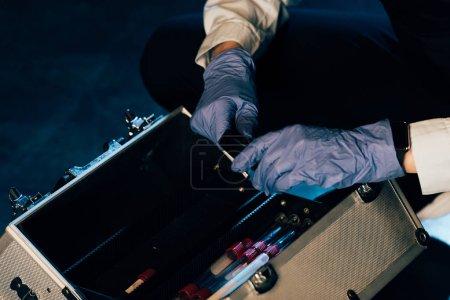 Photo pour Vue recadrée de l'enquêteur dans des gants de caoutchouc avec trousse d'enquête sur les lieux du crime - image libre de droit