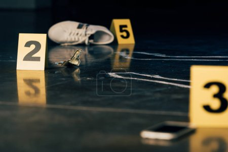 Photo for Selective focus of smartphone, chalk outline, shoe, dollar banknote and evidence markers at crime scene - Royalty Free Image