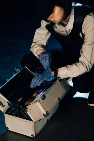 Photo for Cropped view of investigator in cap with investigation kit at crime scene - Royalty Free Image