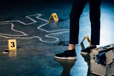Foto de Partial view of investigator standing near chalk outline and evidence markers at crime scene - Imagen libre de derechos