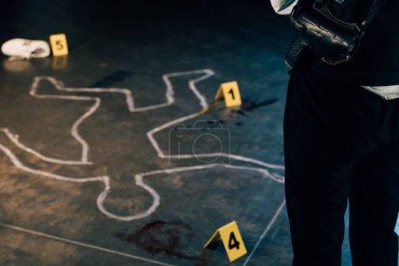 Photo pour Vue recadrée de l'enquêteur debout près du contour de la craie et des marqueurs de preuves sur les lieux du crime - image libre de droit