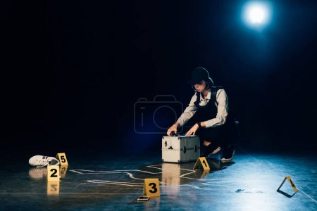 Photo for Investigator with investigation kit near chalk outline at crime scene - Royalty Free Image