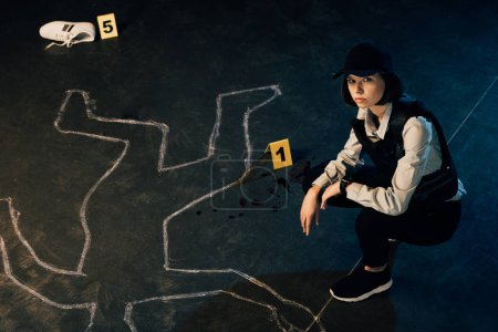 Photo pour Overhead view of investigator near chalk outline and evidence markers at crime scene - image libre de droit