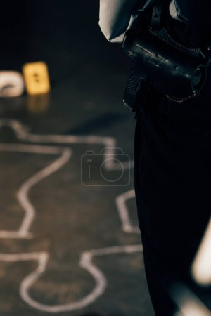 cropped view of investigator with gun at crime scene