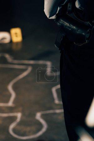 Photo pour Vue recadrée de l'enquêteur armé sur les lieux du crime - image libre de droit