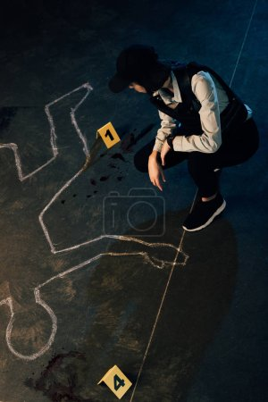 Photo for Overhead view of investigator near chalk outline and evidence markers at crime scene - Royalty Free Image