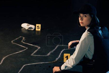 Photo pour Enquêteur assis près de la craie contour à la scène de crime - image libre de droit