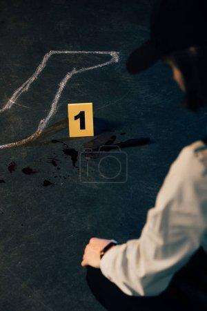 Photo pour Vue recadrée de l'enquêteur près du contour de la craie sur les lieux du crime - image libre de droit
