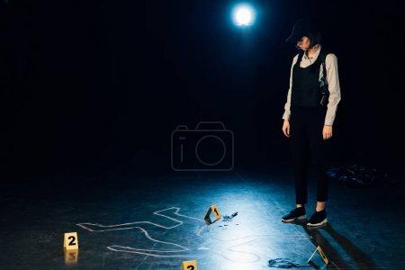 Foto de Full length view of investigator standing near chalk outline at crime scene - Imagen libre de derechos