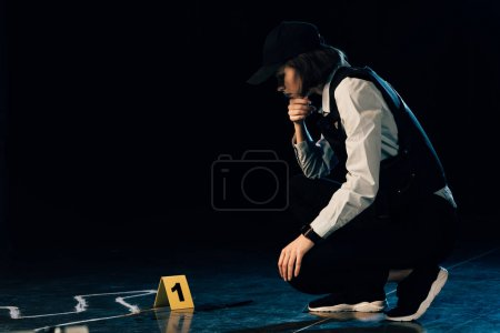 Photo for Investigator sitting near chalk outline at crime scene - Royalty Free Image