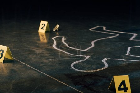 Photo for Selective focus of chalk outline and evidence markers at crime scene - Royalty Free Image