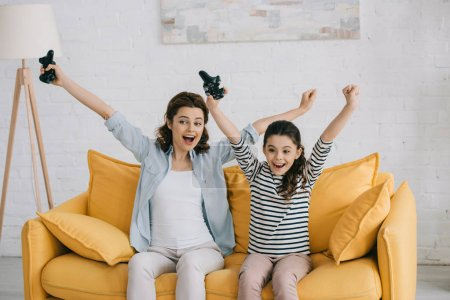 Photo for KYIV, UKRAINE - APRIL 8, 2019: Excited mother and daughter showing yes gesture while sitting on yellow sofa and holding joysticks - Royalty Free Image