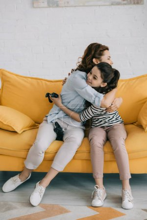 Photo for KYIV, UKRAINE - APRIL 8, 2019: Happy mother and daughter hugging while sitting on sofa and holding joysticks - Royalty Free Image
