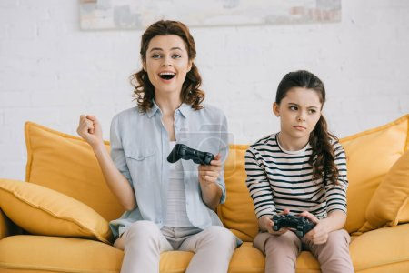 Photo for KYIV, UKRAINE - APRIL 8, 2019: Cheerful mother holding joystick and showing yes gesture while sitting near offended daughter - Royalty Free Image