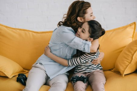 Photo for KYIV, UKRAINE - APRIL 8, 2019: Happy mother and daughter hugging while sitting with joysticks on sofa at home - Royalty Free Image