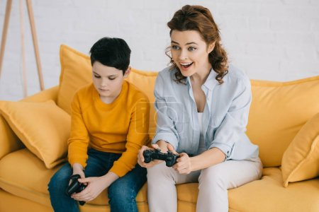 Photo for KYIV, UKRAINE - APRIL 8, 2019: Smiling woman playing video game while sitting near offended son holding joystick - Royalty Free Image